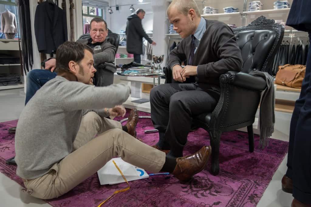 Riccardo mäter en kunds fötter och diskuterar passformsbitar.