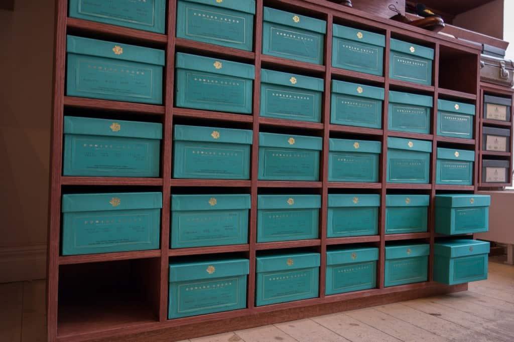 Edward Green-skorna står på en specialbeställd hylla från en göteborgssnickare, där nederdelen är byggd för att rymma skolådor.