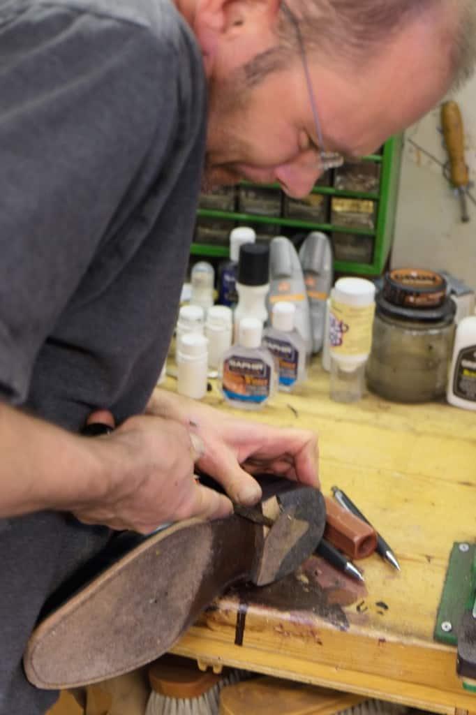 Operationen inleds med att klacken slits bort. Först den yttersta läderbiten. Under den finner vi fiberplatta.