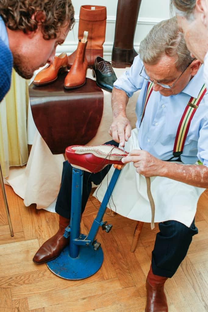 Janne Melkersson randsyr en skor, och nyfikna besökare närgranskar.