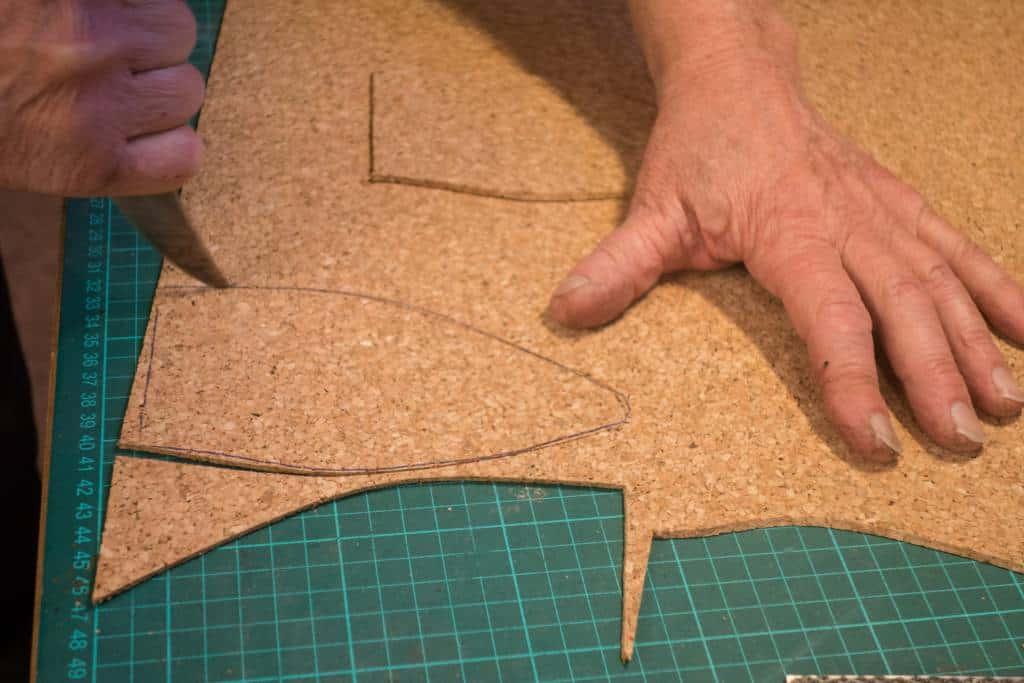 En bit kork skärs ut från en tunn korkplatta ,som ska användas som fyllnad mellan bindsula och slitsula. Som sagt blir hålrummet rätt litet på handrandsytt, bespokeskomakare använder oftast korkplattor eller filt för detta, ibland poröst läder. Det är ovanligare med den korkmassa som vanligtvis nyttjas i fabriker.