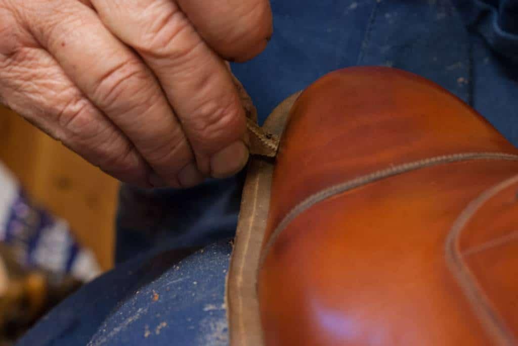 Här det lilla klipska, hemmagjorda verktyget som markerar var man ska skära sulan, så det blir jämnt. En läderbit med en spik i.