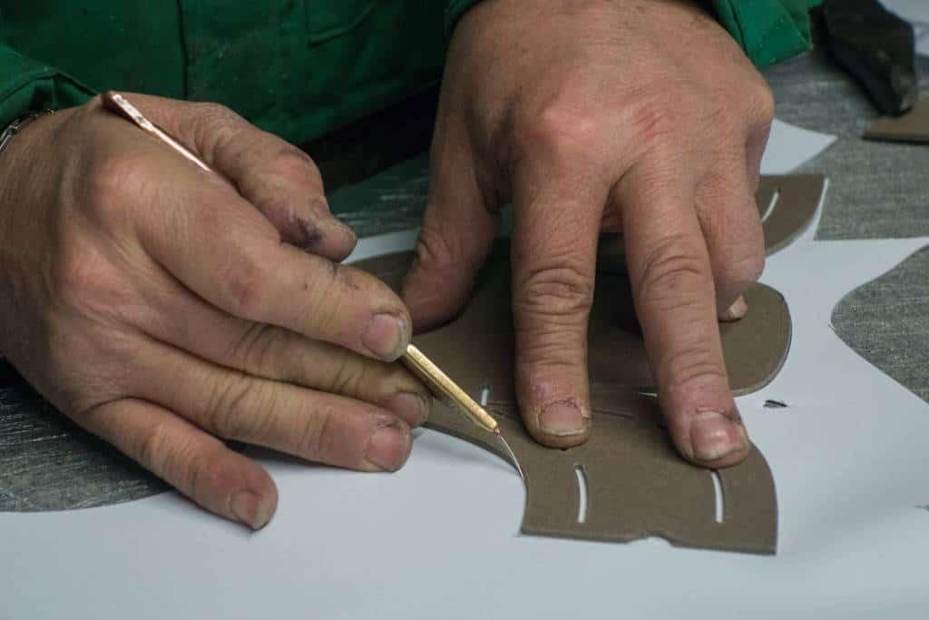 Här från tillskärningen av ovanlädret till en annan modell. De skåror man ser i schablonen ritar man med en speciell läderpenna i, för att markera var den del som biten ska sys ihop med ska överlappa.