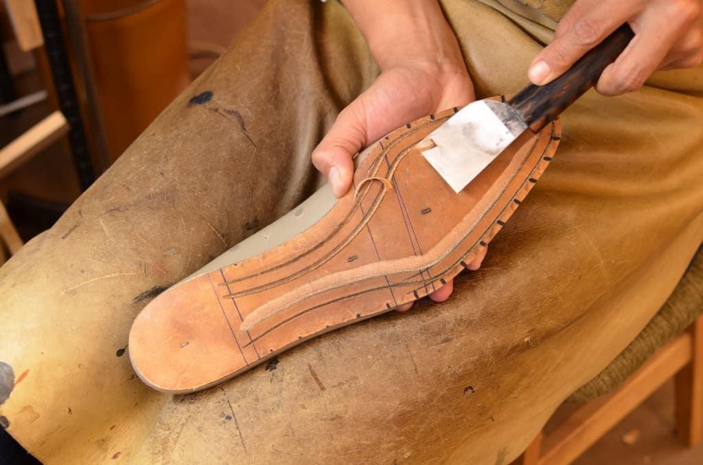 Sedan karvas läppen som randsömmen ska sys i ut. Den här typen av kniv är lite speciell, och används genom att man trycker framåt istället. Japanerna använder den sortens kniv för många moment i tillverkningen.